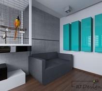Grafitowa kanapa na lekko szarej ścianie z dodatkiem akcentu kolorystycznego w postaci frontów szafek.