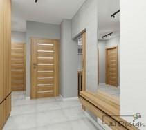 Przestronny salon w szarościach z dużym lustrem, które daje iluzję jeszcze większej przestrzeni.