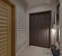 Oryginalny korytarz z szerokimi, ciemnymi drzwiami wejściowymi do mieszkania.