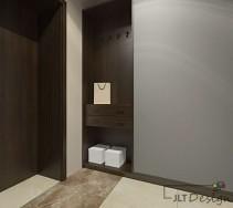 Jasna szarość na ścianach projektu korytarza z ciemną wnęką zastępującą meble.