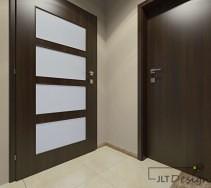 Połączenie jasnego, stonowanego koloru ścian z ciemnymi drzwiami w aranżacji przedpokoju.