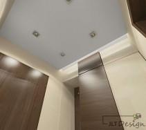 Elegancki korytarz z kontrastującymi frontami i drzwiami w ciemnym kolorze na tle beżu ścian ze zdobieniami sufitu.