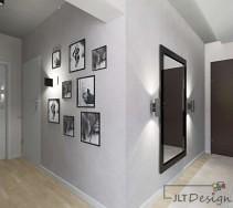 Duży jasny, korytarz z jasną ścianą w odcieniu szarości na której umieszczono obrazy oraz lustro w czarnych ramach.