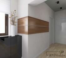 Duży, jasny projekt korytarza . Na ścianie drewniana dekoracja w kolorze naturalnego drewna, obok ciemna komoda.