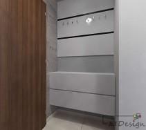 Niewielki korytarz z ciekawie zagospodarowanym miejscem na garderobę oraz półkę na buty w neutralnym odcieniu szarości.