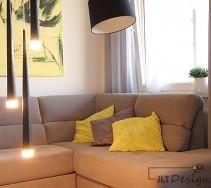Czarna stojąca lampa i zwisające lampki sufitowe w salonie