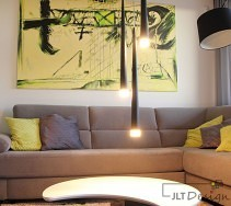 Asymetryczny stolik, szara kanapa i duży asymetryczny obraz w salonie