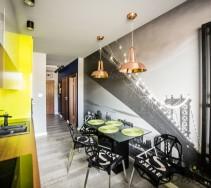 Realizacja wnętrza kuchni w apartamencie - widok efektownej ściany kuchni ze stołem.