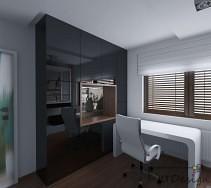Białe biurko oraz fotel kontrastują z połyskującą czernią na ścianie obok.