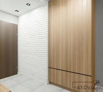 Ciekawa faktura jasnej ściany korytarza oraz szafa w kolorze drewna.