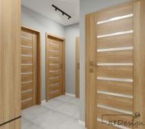 Przestronny korytarz w szarości z dominującym, jasnym odcieniem drzwi.
