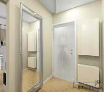 Kremowy korytarz z dużym lustrem i białymi drzwiami wejściowymi.