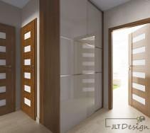 Jasny korytarz z dużą szafą z frontami w odcieniu zbliżonym do odcienia ścian.