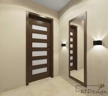 Elegancki korytarz z dużym lustrem i drzwiami wykończonymi ciemnym drewnem.