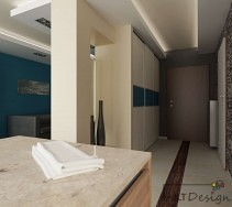 Otarty przedpokój z drzwiami wejściowymi w kolorze czekolady oraz jasno beżowymi frontami szafy wzbogaconej o niebieski wzór nawiązujący do wnętrza salonu.