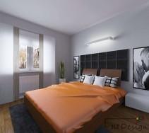 Nowoczesna sypialnia z czarnym pikowaniem na ścianie i pomarańczowymi dodatkami