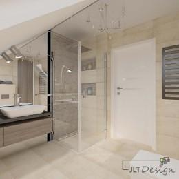 Prysznic oddzielony szkłem i umywalka pod skosem w łazience na poddaszu