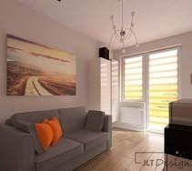 Szara kanapa na przeciwko okna z drzwiami balkonowymi w niewielkiej, jasnoszarej sypialni wypełnionej dziennym światłem.
