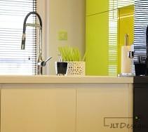 Aranżacja kuchni z meblami w kolorze bieli czerni i limonki