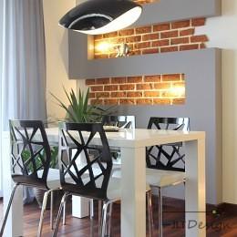 Kącik jadalniany z czarną lampą i ażurowymi krzesłami